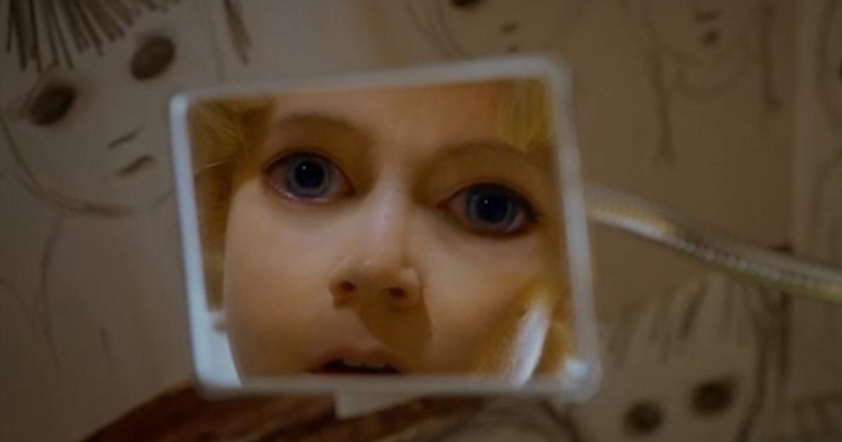 la protagonista si specchia e vede il suo volto con gli occhi grandi come i suoi ritratti - nerdface