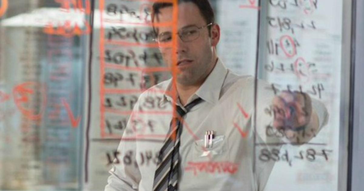 ben affleck in camicia bianca sta scrivendo qualcsao su una lavagna in vetro già ricca di numeri - nerdface