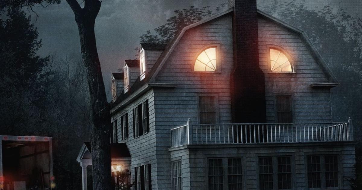 la casa di amityville in piena notte e con alcune finestre illuminate sembra un volto demoniaco - nerdface