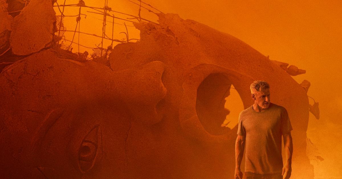 harrison ford cammina in una desolante landa spoglia e gialla, sullo sfondo la testa reclinata di una statua enorme - nerdface