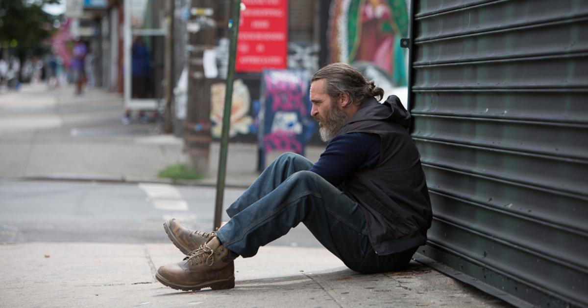 il protagonista è seduto a terra, schiena su una serranda - nerdface