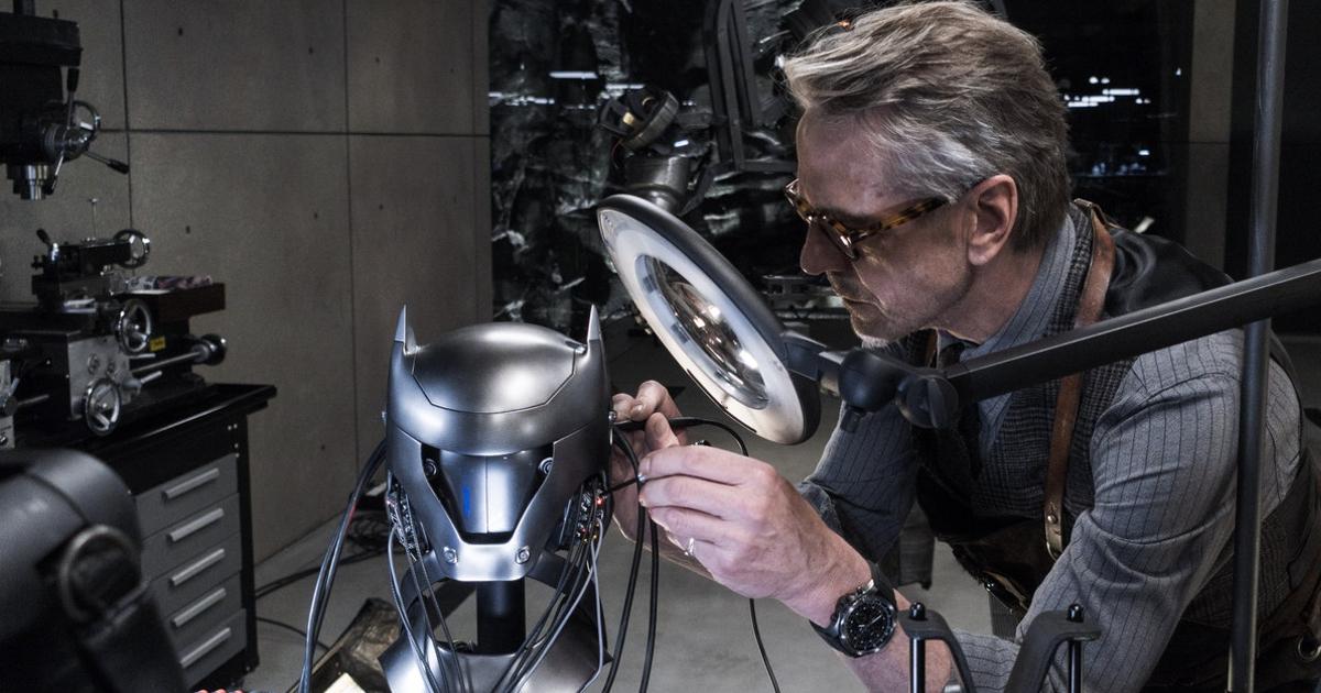 jeremy irons è alfred e osserva alla lente una maschera rinforzata per batman - nerdface