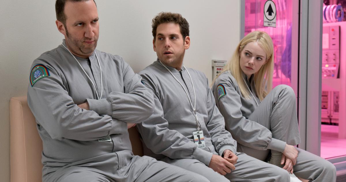 i due protagonisti sono in divisa grigiaq e sono seduti su una panca in una sorta di cella, guardano un terzo che alza gli occhi in segno di noia - nerdface