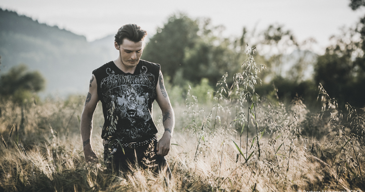 il protagonista cammina malinconico guardando in basso in mezzo a una campo di erba alta - nerdface