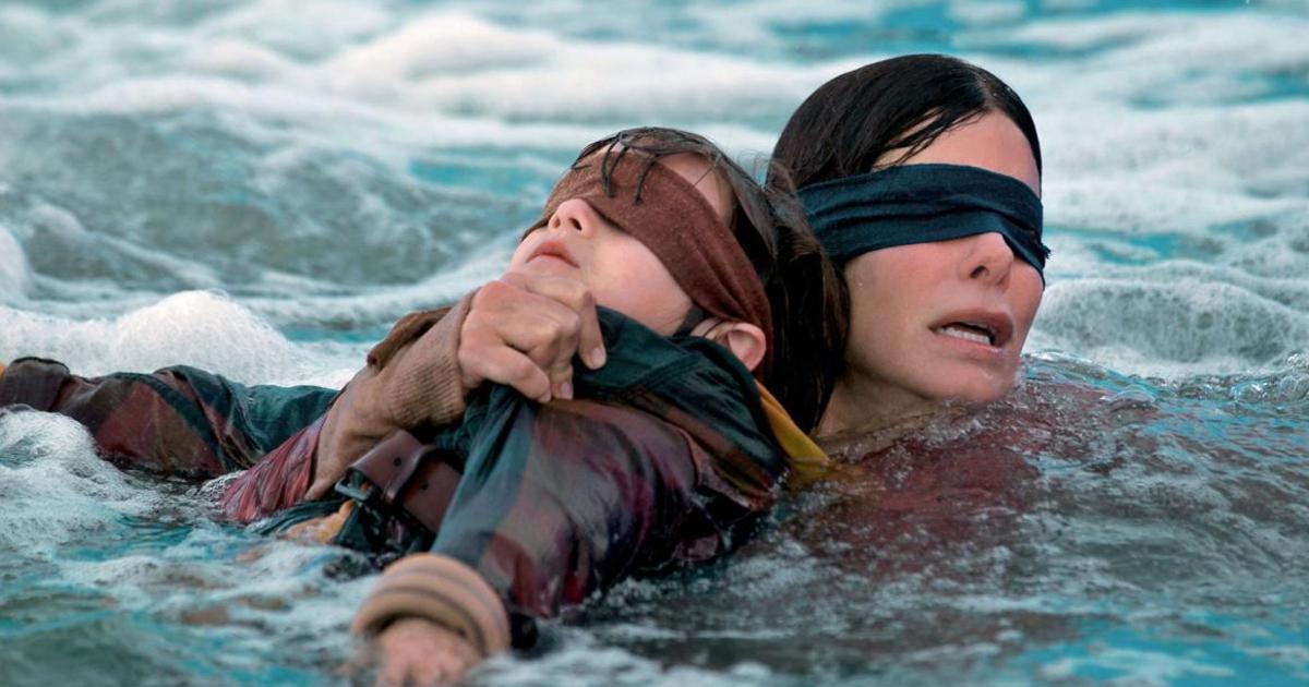 sandra bullock, bendata, tiene un bambino anch'esso bendato e cerca di guadare un fiume - nerdface