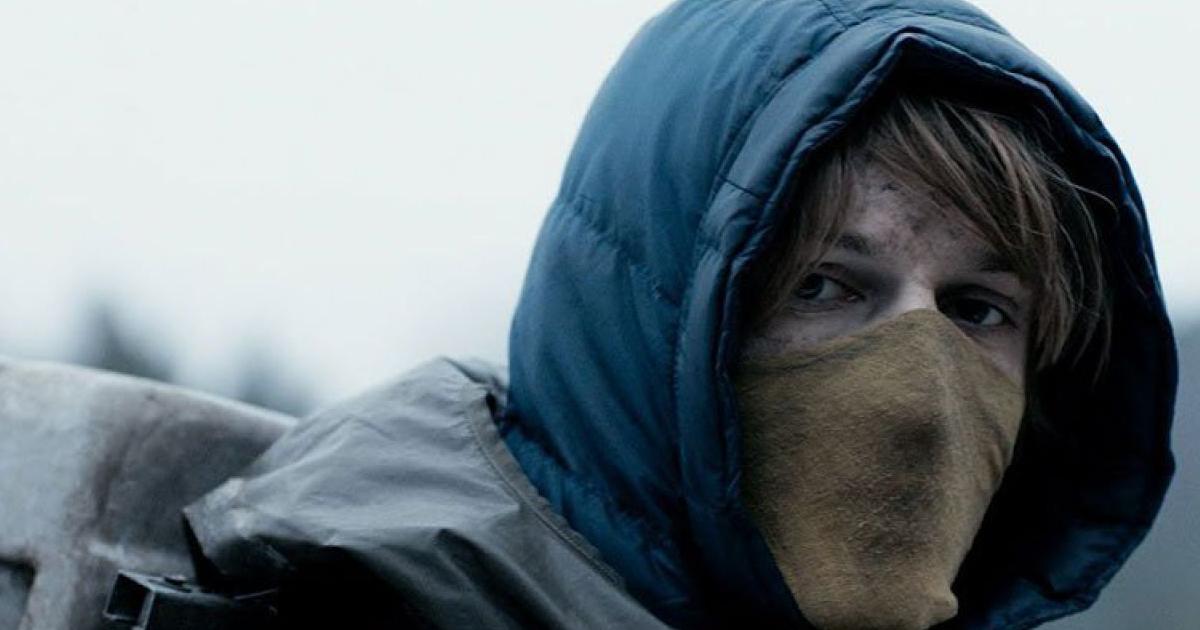 un ragazzo incapucciato e con un pezzo di stoffa a coprire bocca e naso si volta e osserva in camera - nerdface