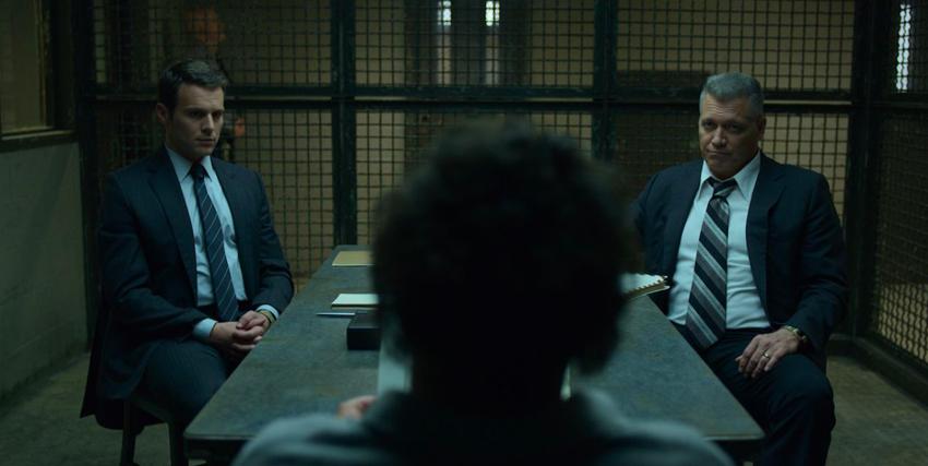 i due investigatori stanno interrogando un uomo in carcere, ripreso di spalle - nerdface