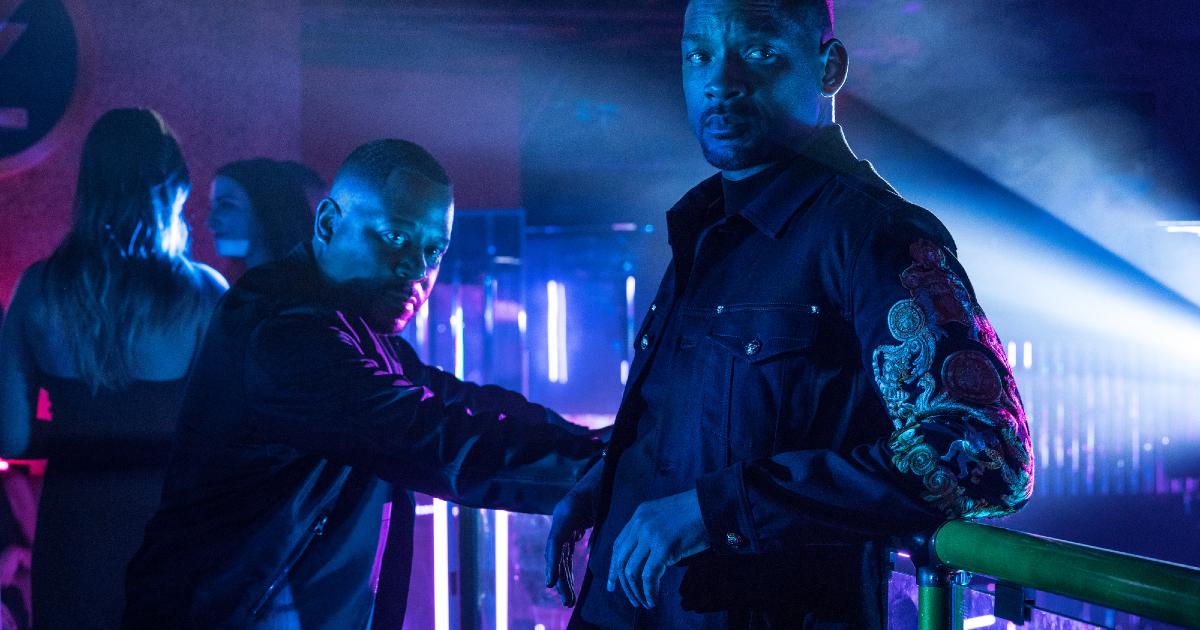 i due protagonisti sono poggiati sul bancone di un bar illuminato di luce blu - nerdface