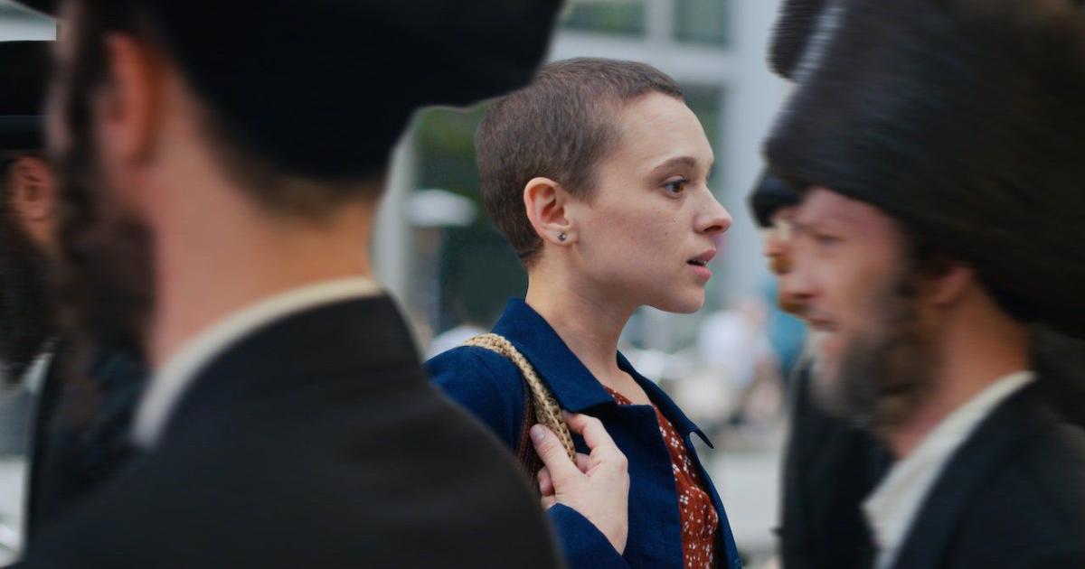 la protagonista completamente rasata cammina in direzione contraria agli uomini della sua comunità vestiti in abiti tradizionali - nerdface