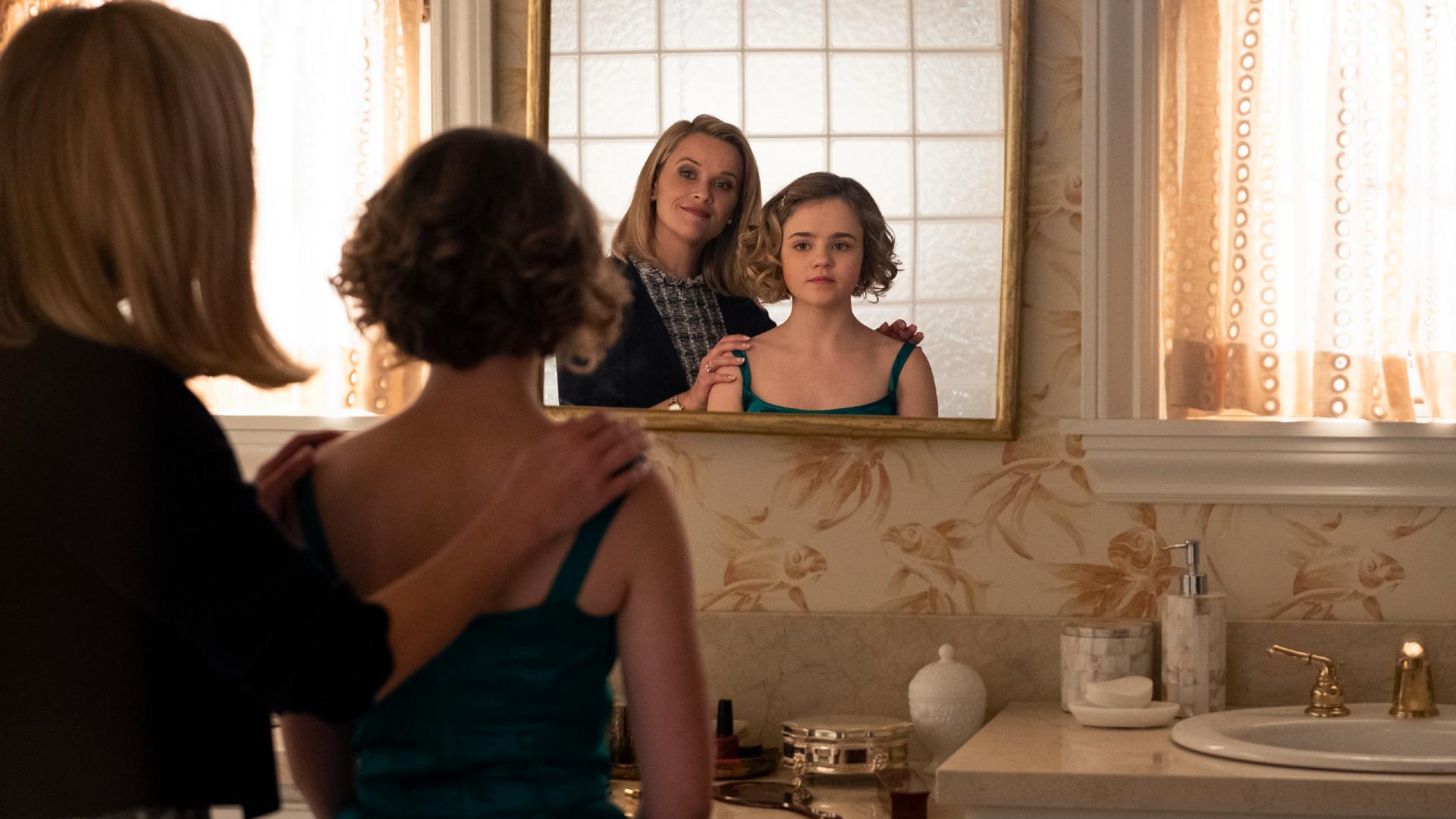 madre e figlia sono davanti uno specchio: la donna sorride, la giovane sembra più perplessa - nerdface