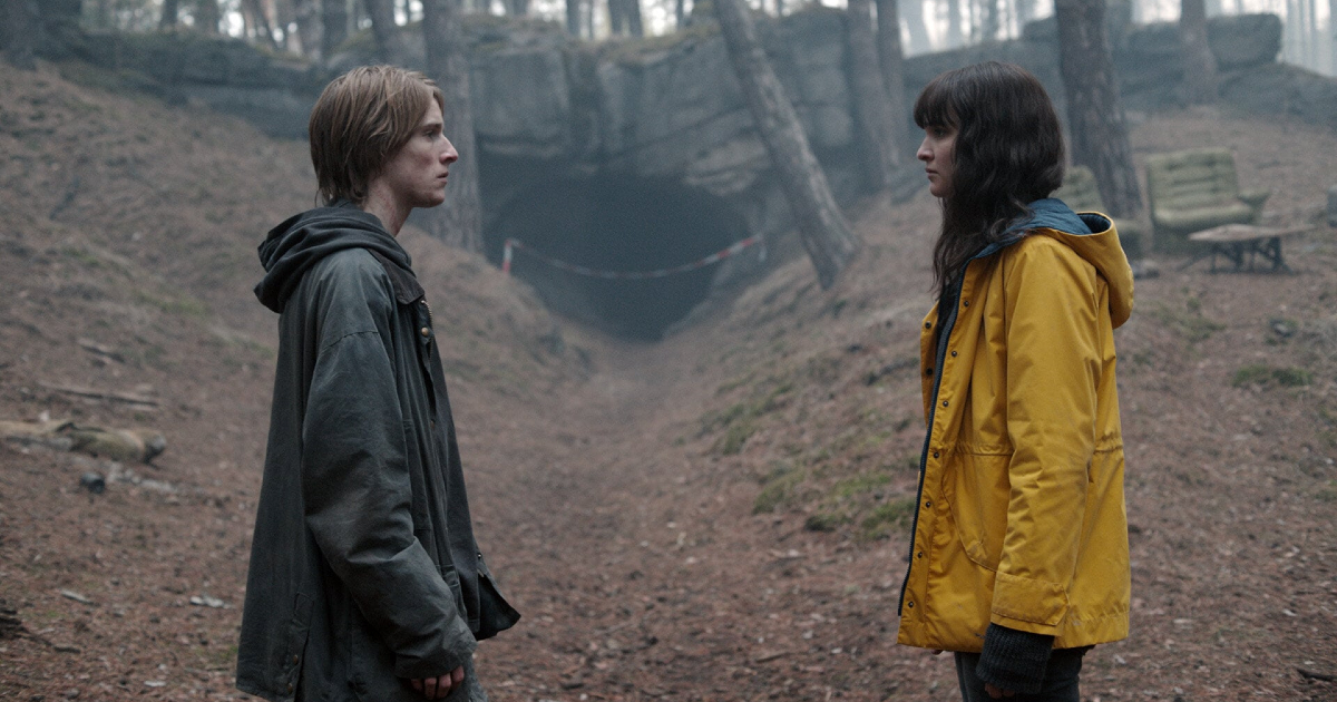 i due protagonisti si guardano, mentre sono di fronte a una grotta - nerdface