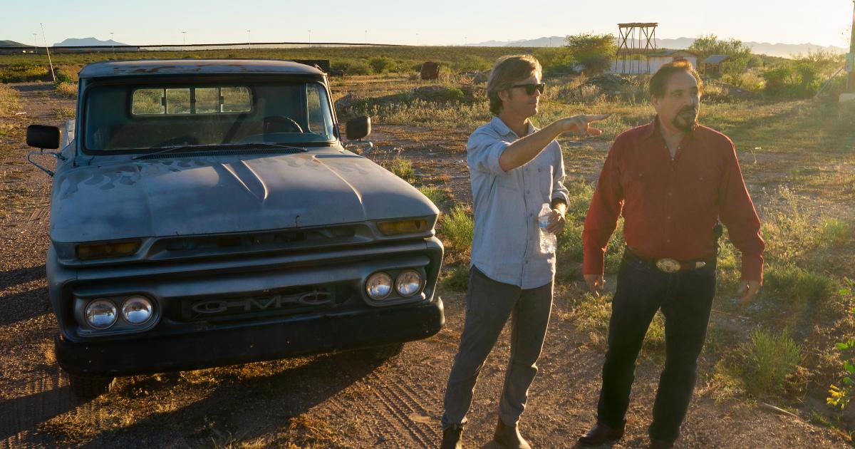l'ex agente hector berellez e un altro uomo sono davanti un pick up e guardano un luogo davanti a loro - nerdface
