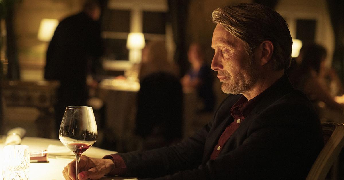 mads mikkelsen osserva una calice di vino bianco - nerdface