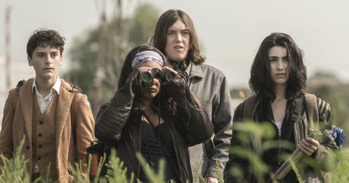 una ragazza guarda qualcosa al binocolo, gli altri tre osservano preoccupati - nerdface