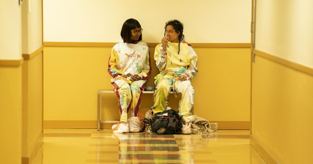 due giovani ragazze sono sedute in fondo a un corridoio: indossano la stessa tuta, mangiano e si guardano - nerdface