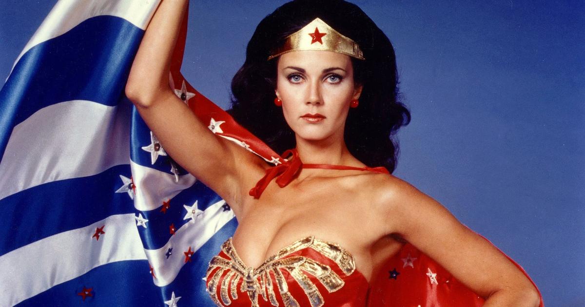 lynda carter nella celebre posa di wonder woman che tiene la bandiera americana - nerdface