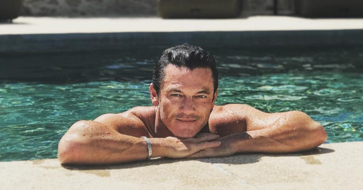 luke evans è immerso in una piscina ma si tiene ai bordi sulle braccia e sorride - nerdface