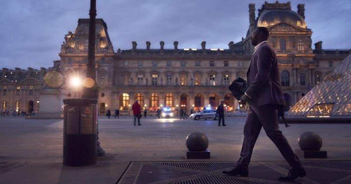 omar sy cammina sornione all'esterno del louvre, la sera - nerdface