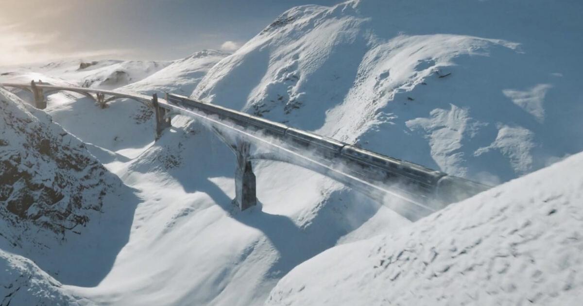 il treno corre veloce su un ponte che si staglia tra due monti innevati e ghiacciati - nerdface