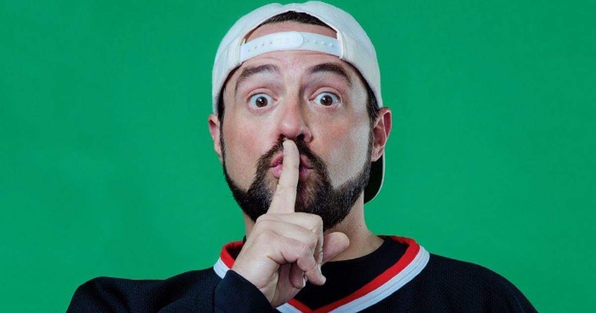 kevin smith col cappel,lino al contrario fa il segno del silenzio col dito davanti la bocca - nerdface
