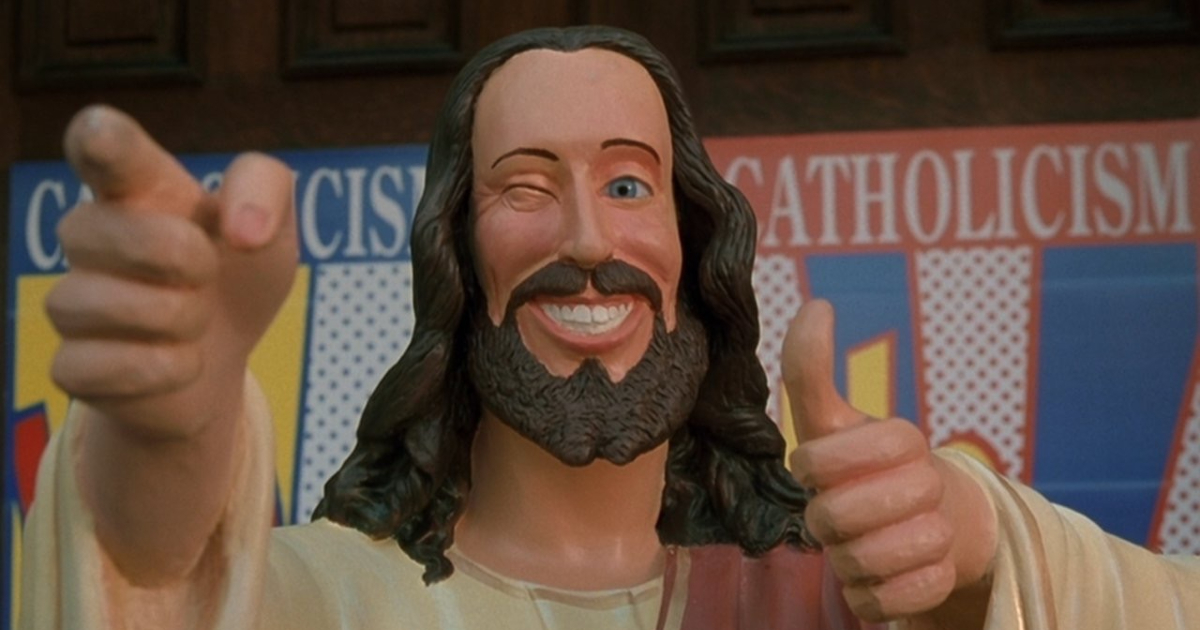 il cristo compagnone di dogma, satira su chi lucra intorno alla religione, è raffigurato in una statua che strizza l'occhio e fa l'ok - nerdface
