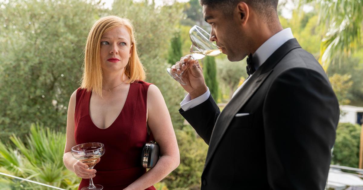 un uomo e una donna a un party, mentre bevono da un calice, si guardano con malizia - nerdface