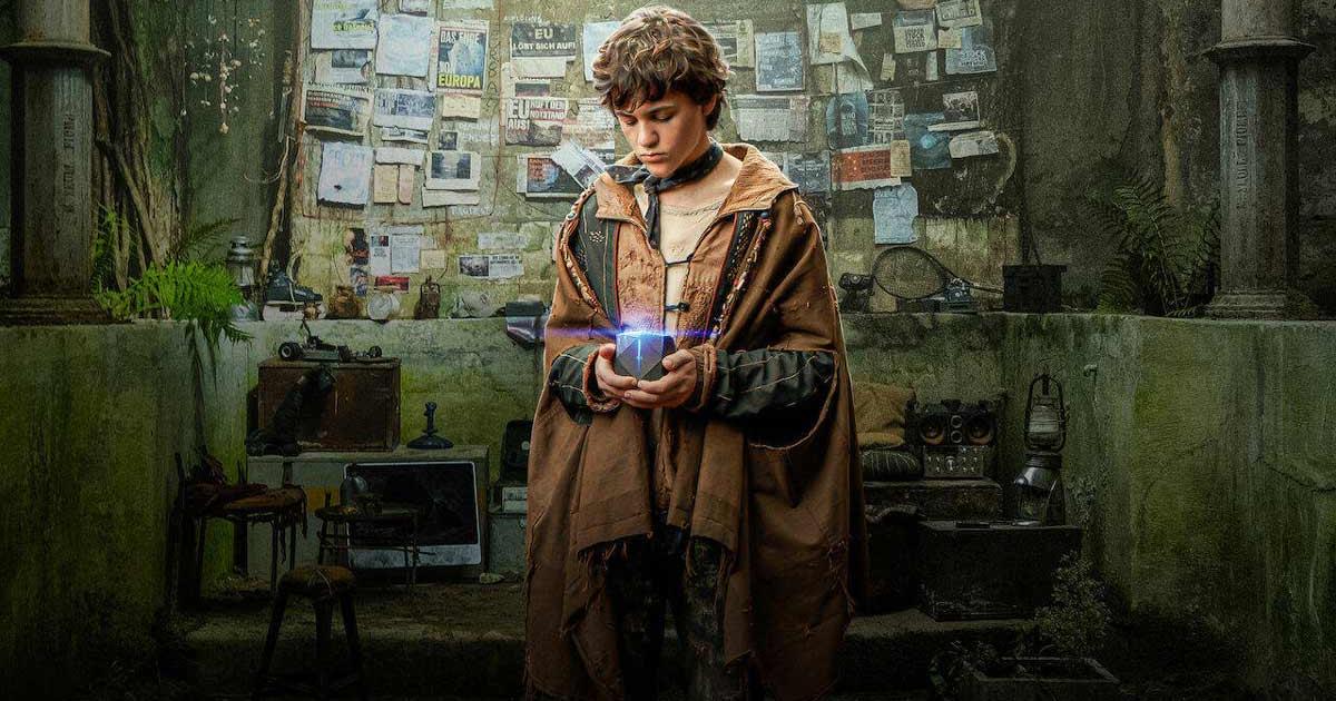 uno dei tre fratelli, vestito di tracci, tiene in mano un cubo luminoso - nerdface