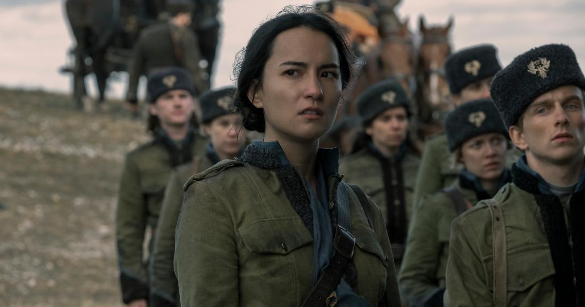 in divisa militare, la protagonista p insieme ad altri sodlati e guarda alla sua destra, preoccupata - nerdface