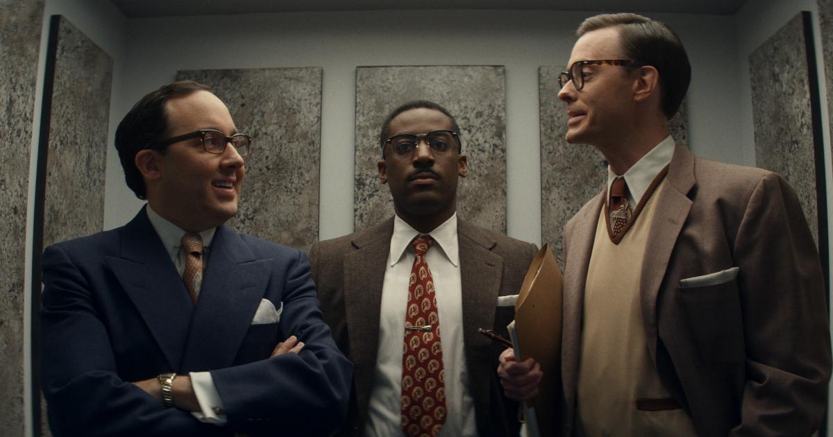 un uomo di colore è in ascensore insieme a due bianchi che parlano tra loro e lo ignorano - nerdface