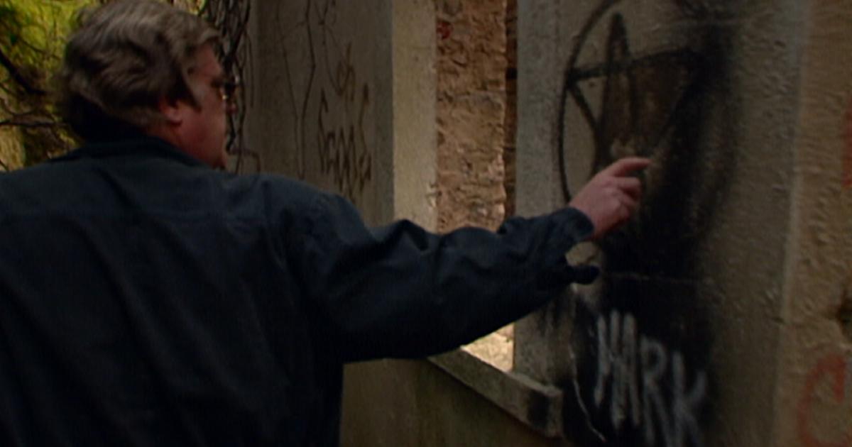 un uomo indica un pentacolo pitturato su un muro - nerdface