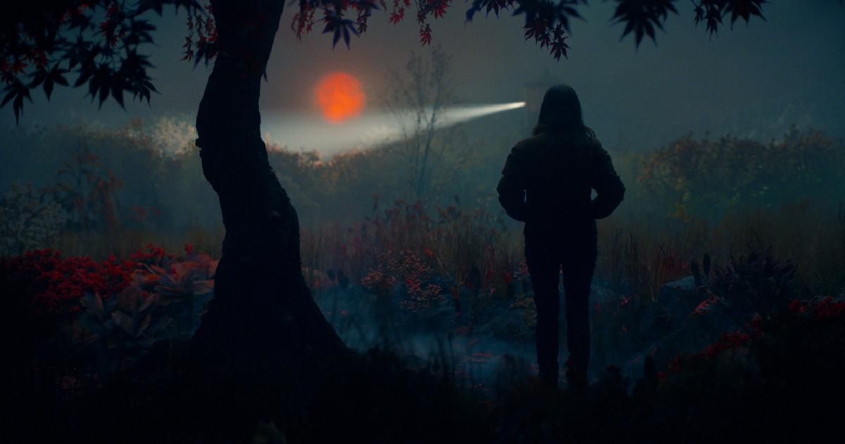 la key art di lisey's story mostra la protagonista, di notte, mentre guarda una faro dietro al quale una luna arancione fa capolino - nerdface