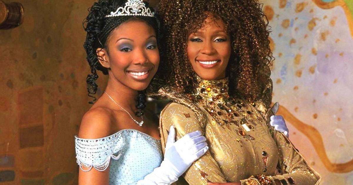In Cenerentola di Rodgers e Hammerstein, Brandy, che interpreta Cenerentola, abbraccia Whitney Houston vestita in oro. entrambe sorridono.
