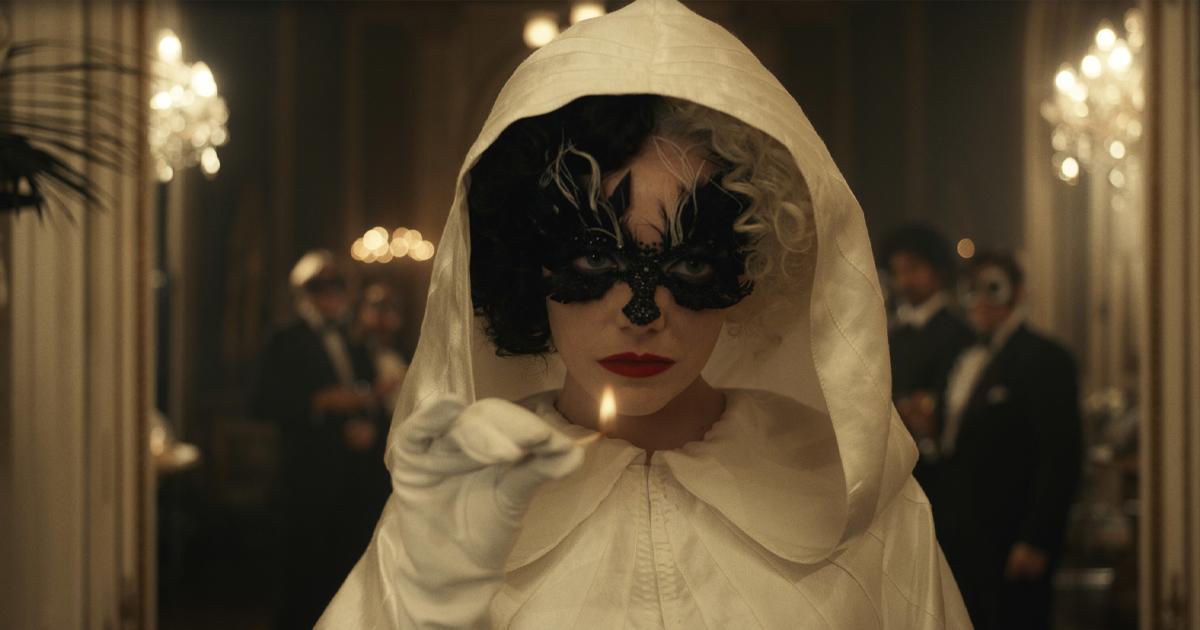Un primo piano di Crudelia interpretata da Emma Stone: vestito e cappuccio bianco in testa, mascherina nera sugli occhi e gli inconfondibili capelli bicolore.