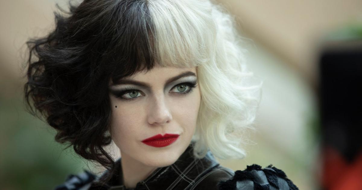 Un primo piano di Emma Stone, che interpreta Crudelia. Sguardo intenso, labbra rosso fuoco, capelli metà bianchi e metà neri con la frangetta.