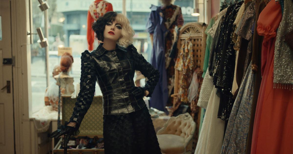 Emma Stone interpreta Crudelia. In questa scena del film, vestita di nero, con le mani sui fianchi in un Atelier di moda.