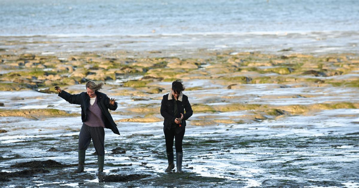 due protagonisti del film camminano e ridono su una secca del mare - nerdface