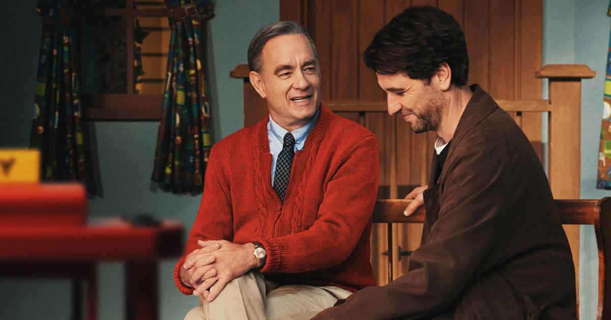 tom hanks interpreta fred rogers e siede accanto al giornalista che lo deve intervistare, entrambi sorridono - nerdface