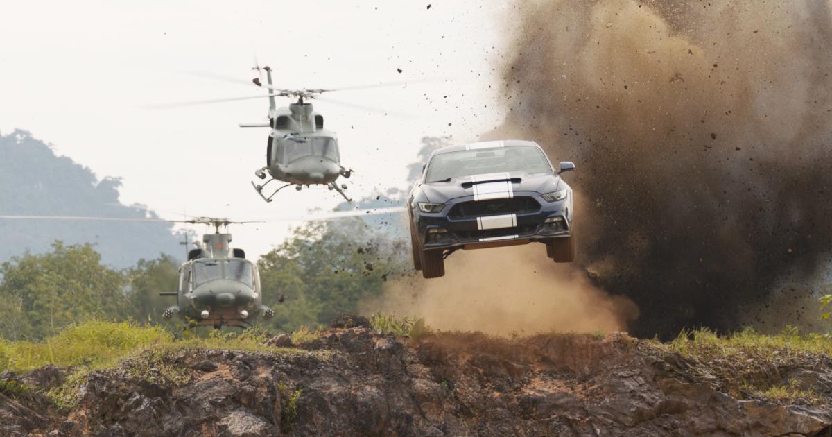 una mustang nera con due bande biuanche sul cofano decolla da un dirupo, inseguita da due elicotteri - nerdface