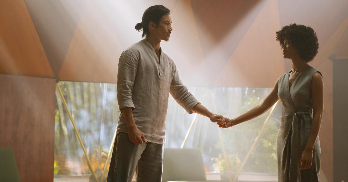 un uomo e una donna si prendono la mano, uno di fronte all'altra, all'interno di un tendone - nerdface