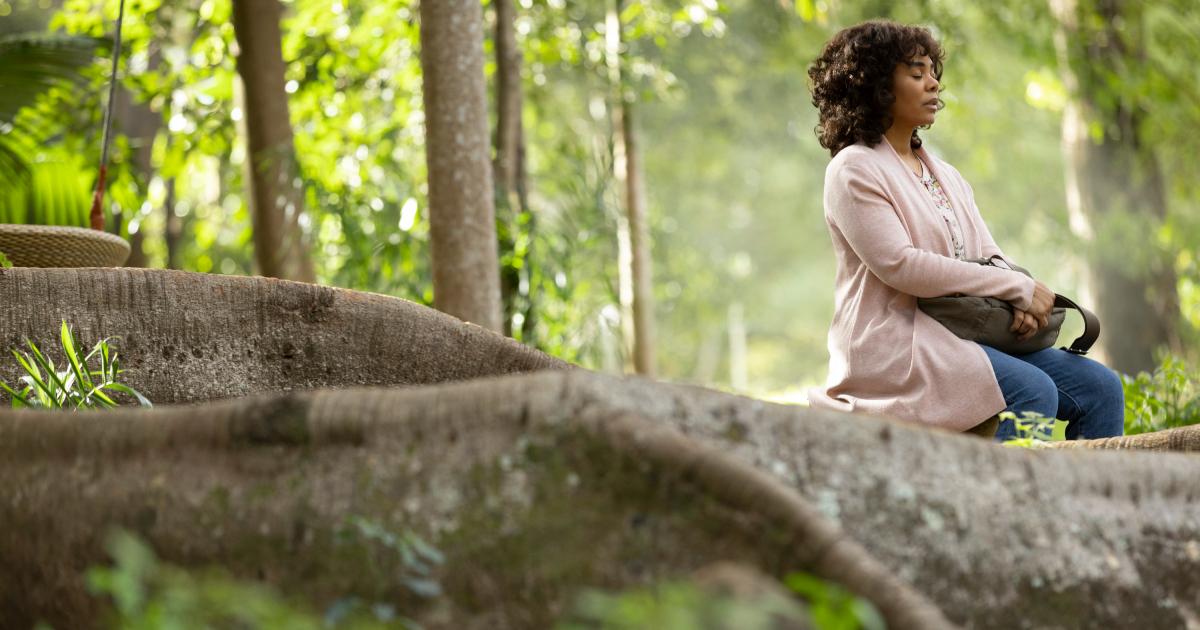 una donna sta meditando in mezzo a un bosco - nerdface