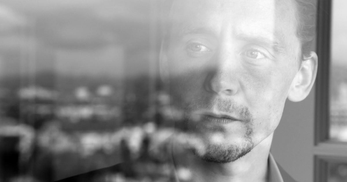 Primo piano di Tom Hiddleston tra i riflessi di una finestra - nerdface