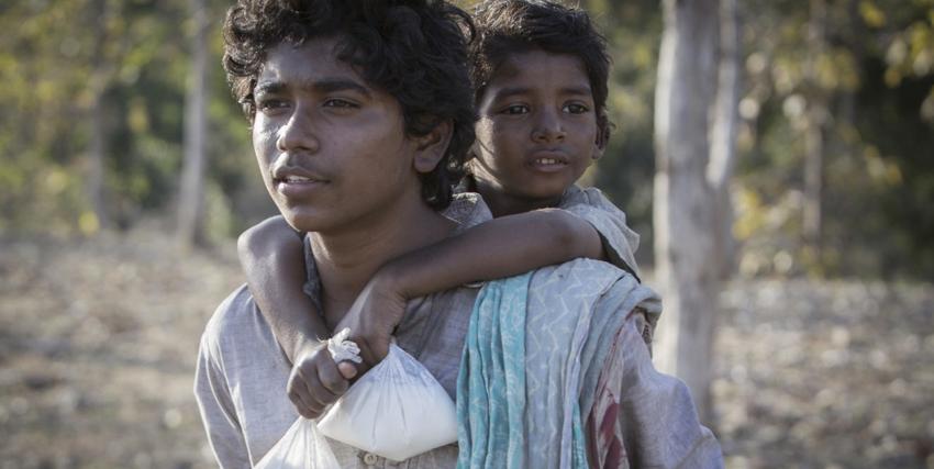 Recensione Lion: una scena del film. Lion bambino sulle spalle del fratello