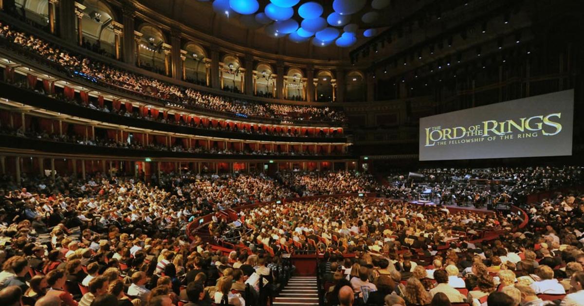 una sala concerti gremita sta assistendo alle musiche dal vivo del ritorno del re mentre sullo schermo è proiettato il film - nerdface
