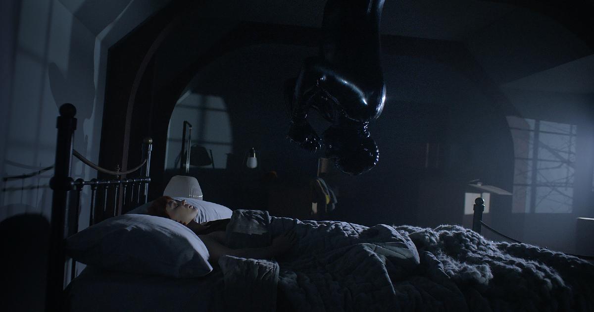 una donna interamente in latex nero si cala sopra il letto sul quale dorme una ragazza - nerdface
