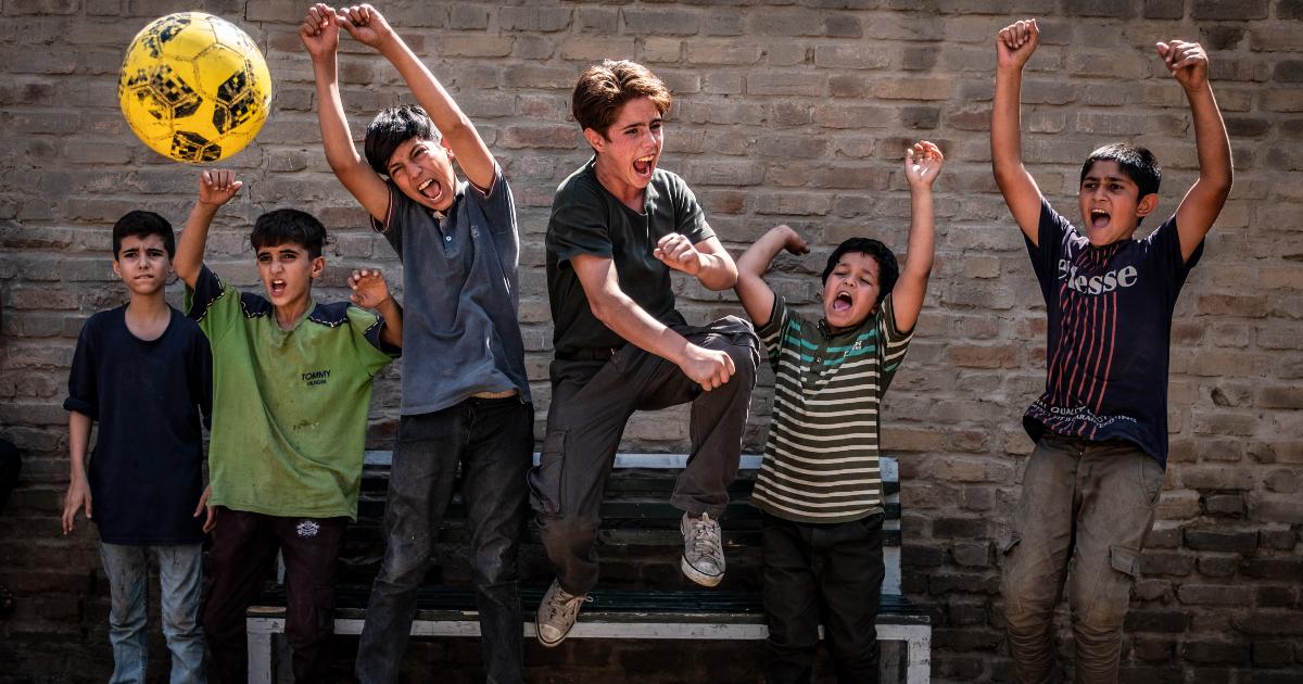 i giovani protagonisti esultano mentre giocano con un pallone giallo - nerdface