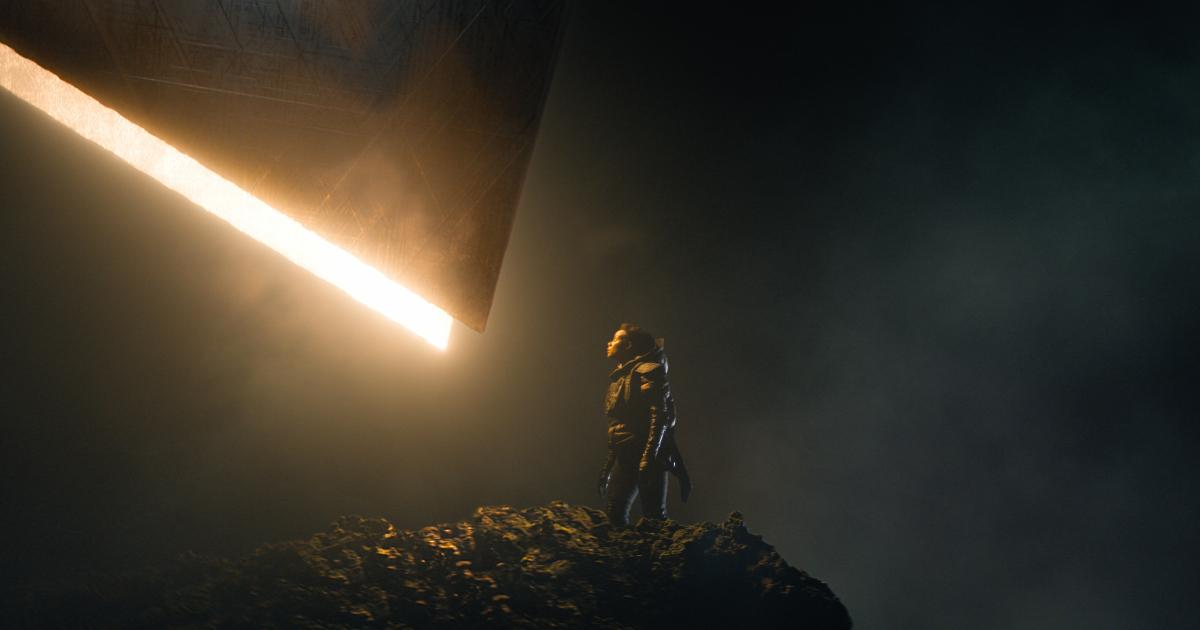 un'immagine suggestiva di fondazione vede una giovane osservare una lama di luce fuoriuscire da una parete nera - nerdface