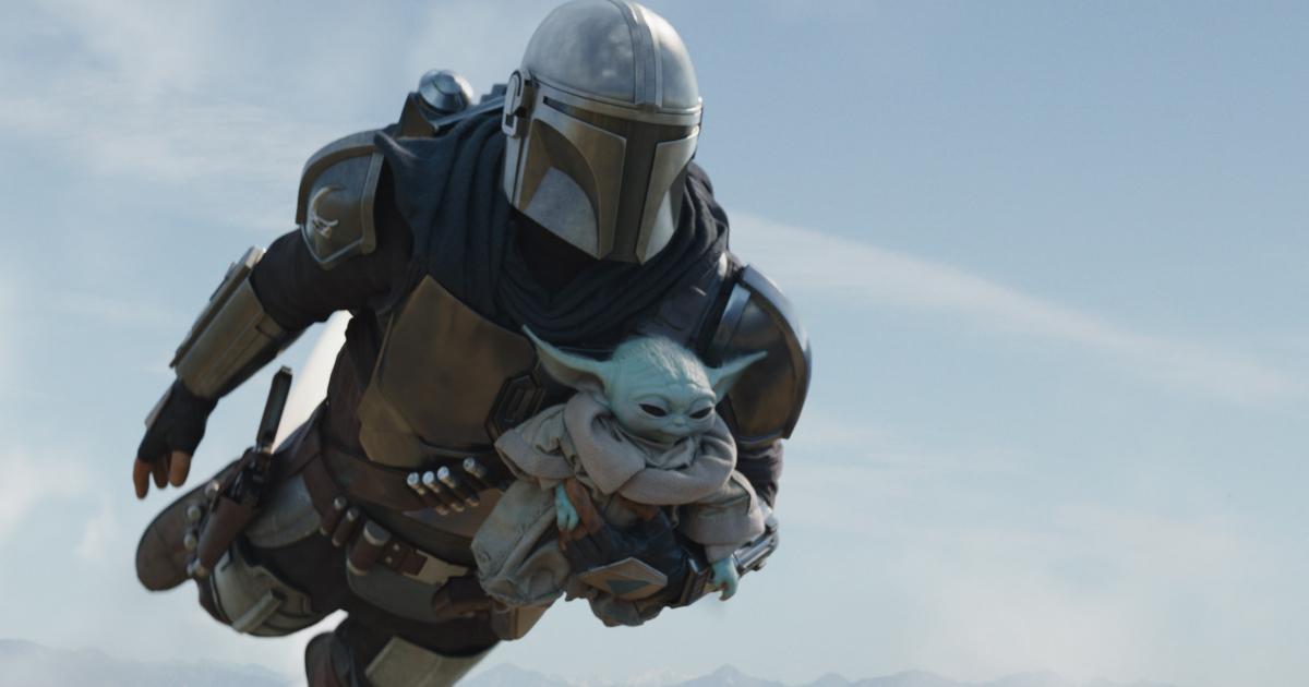 il mandalorian è in volo e tiene in braccio baby yoda - nerdface