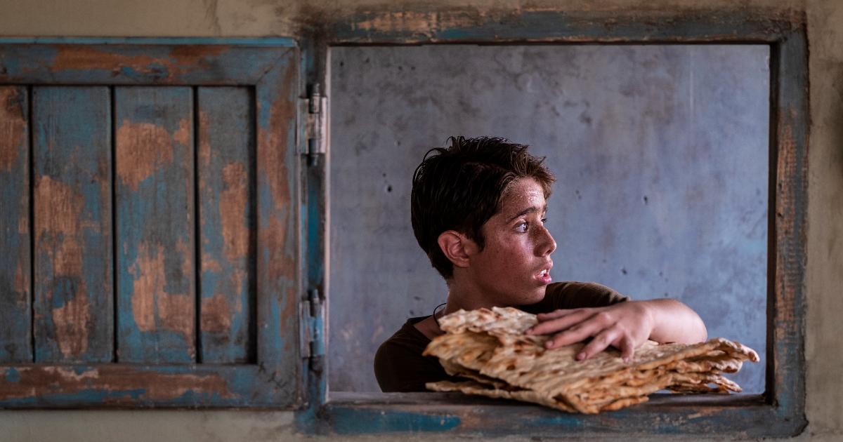 uno dei giovani protagonisti si affaccia dalla finestra di un fornaio con del pane appena pronto - nerdface
