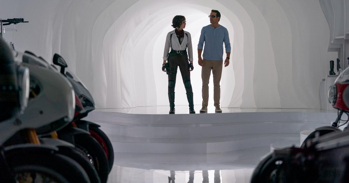 ryan reynolds e una donna sono in hangar bianco pieno di moto da corsa - nerdface
