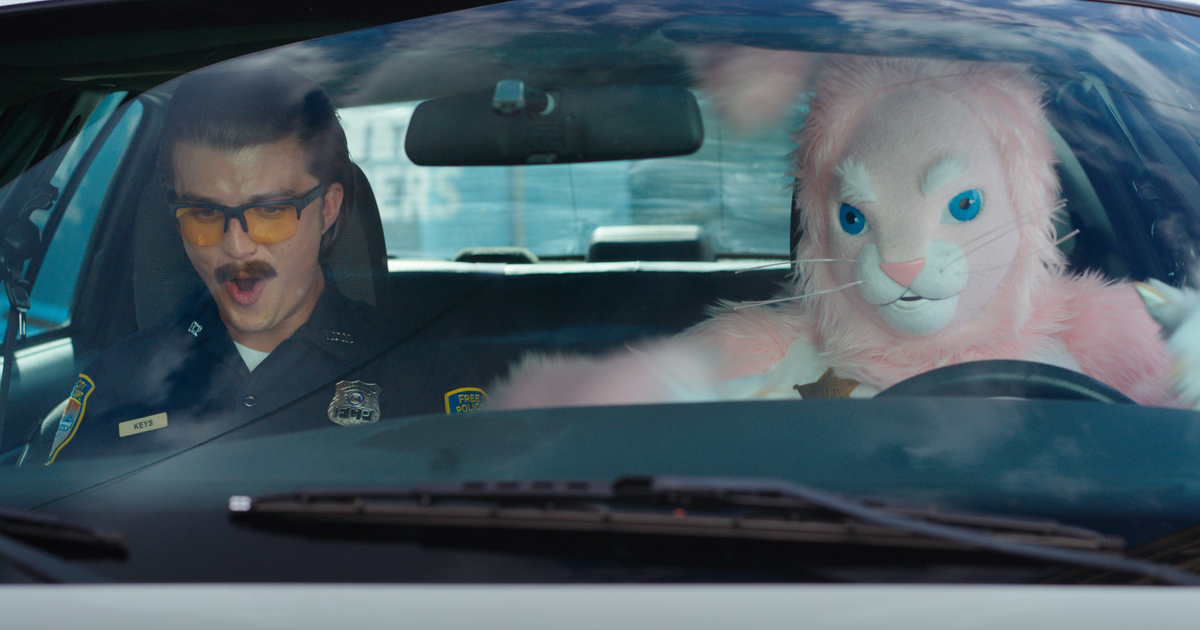 un poliziotto è in macchina co nun uomo vestito da coniglio rosa - nerdface